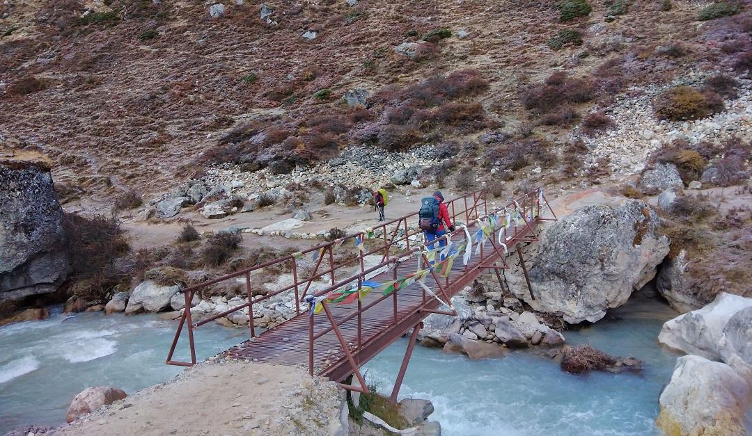 Trekker crossing a bridge near Pheriche